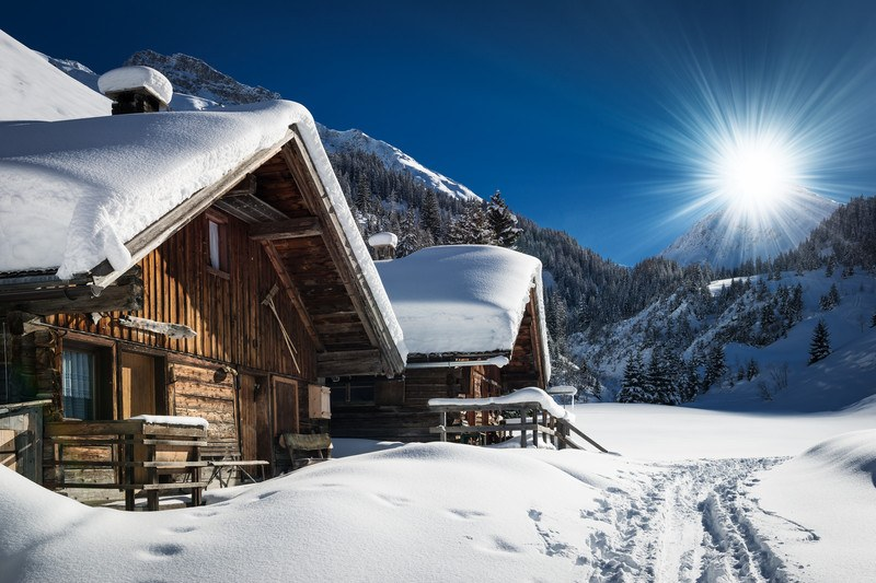 winter cabin with snow on the roof and the sun shining on fresh powder snow and a blue sky