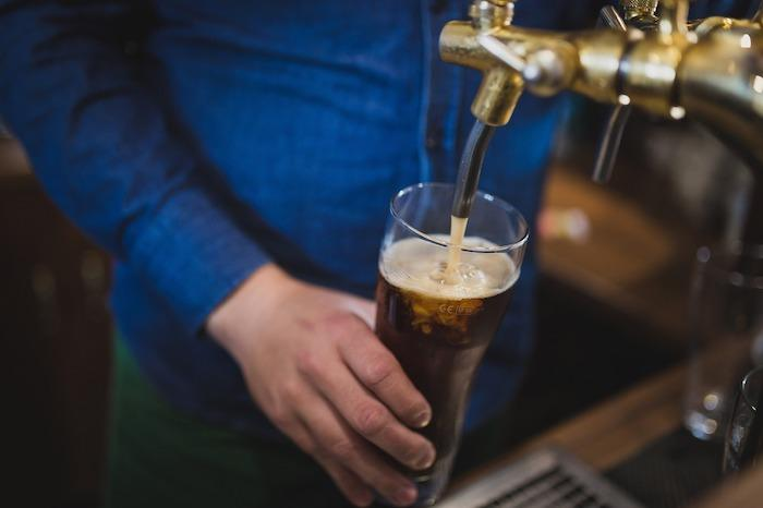man pouring dark lager style beer from a tap in a pub