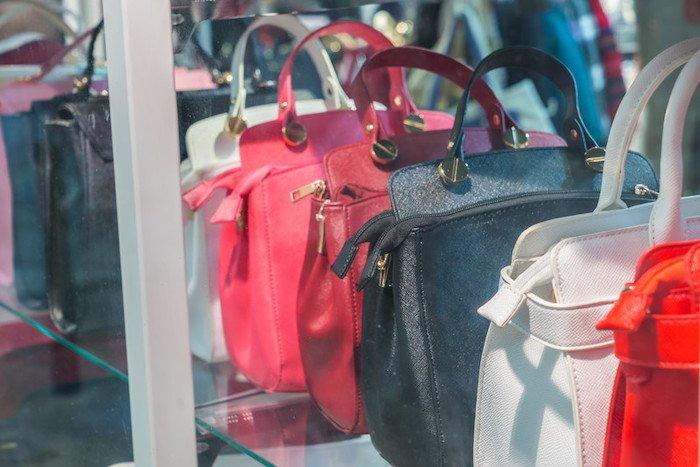 row of designer handbags sitting in a boutique shop