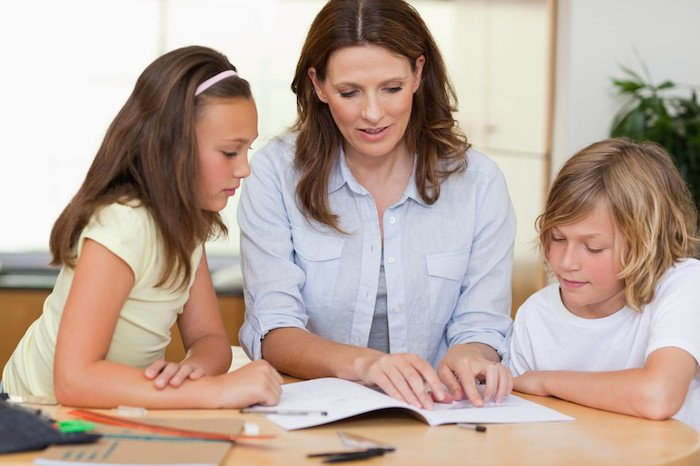 middle aged woman homeschooling two young girls with paper and pen at a desk in their home