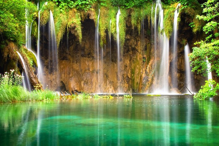 image of waterfall filling a green lagoon