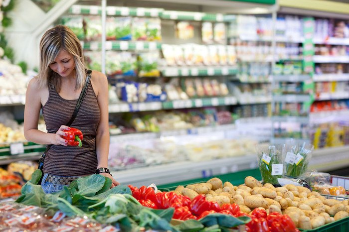 woman looking at red sweet pepper in the grocery store representing the best grocery affiliate programs