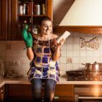 young woman sitting on kitchen counter smiling at a recipe book representing the best recipe affiliate programs