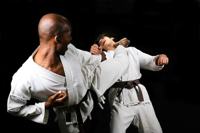 black bald man kicking a white asian man in the throat representing the best martial arts affiliate programs