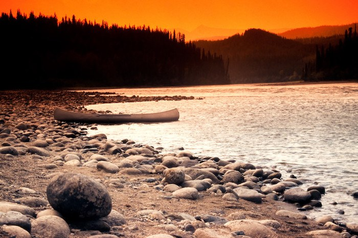 lonely canoe by itself with a sunset lake and mountains in the background representing the best mental health affiliate programs