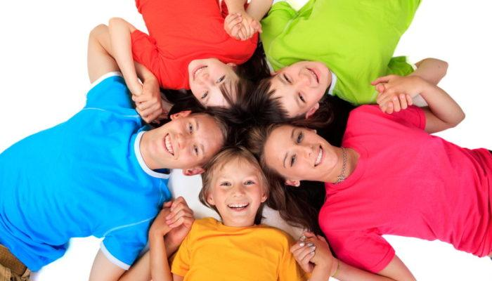 Five young people in brightly-colored tee shirts smile up at the camera, representing the ten best affiliate programs for tee shirts.