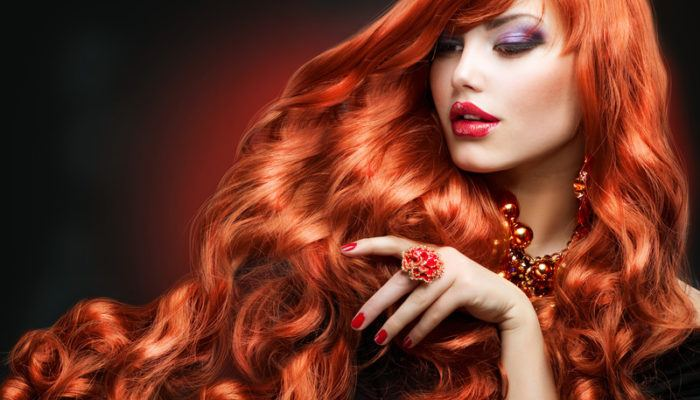 This photo shows a beautiful woman with long red hair, representing the best hair extension affiliate programs.