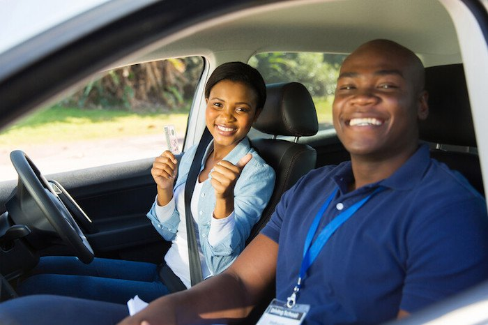 young black woman passing a drivers test with a black driving instructor representing the best african american affiliate programs