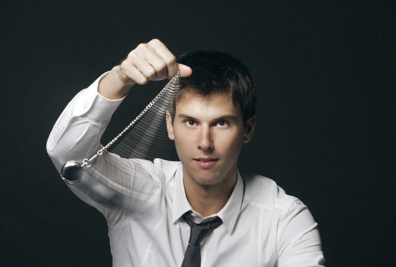 A man in a white shirt with a tie sits in front of a dark background as he swings a watch on a chain, representing the best affiliate programs for hypnosis.