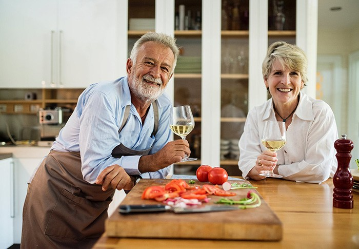 Older couple enjoying wine together in kitchen representing retired people who aren't ready to stop working