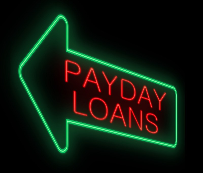A green neon sign in the shape of an arrow contains the words 'payday loans' in red, representing the best payday loan affiliate programs.