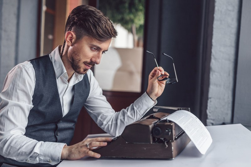A man in a white suit and business vest sits at a table and looks at a paper that he's typing on a vintage typewriter, representing the best screenwriting affiliate programs.