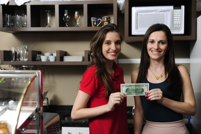 two young women entrepreneurs holding a dollar in a coffee shop representing the best small business loan affiliate programs