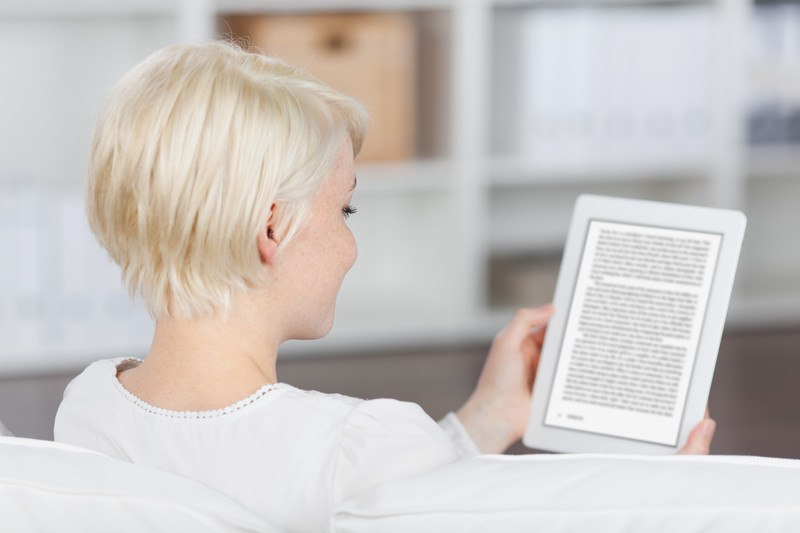 This photo shows a woman with short blonde hair and a white shirt relaxing on a white sofa as she reads an e-book on a tablet, representing the best e-book affiliate programs.