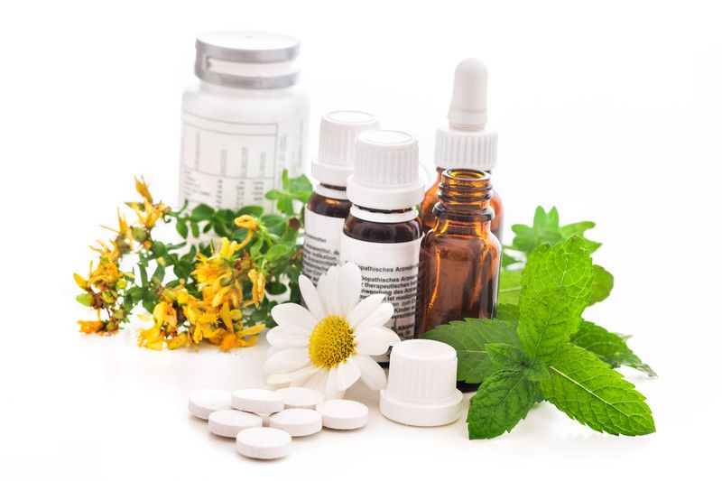 This photo shows some loose pills, flowers and herbs around some bottles of herbal supplements against a white background, representing the best herbal affiliate programs.
