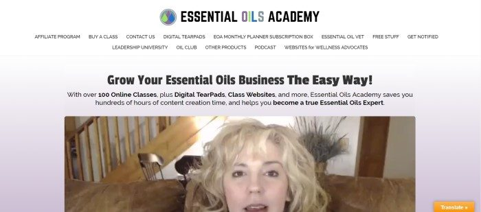 """This screenshot of the home page for Essential Oils Academy has a white background with the logo at the top, the words """"Grow your essential oils business the easy way"""" in black lettering beneath it, and a still shot from video of a woman talking about Essential Oils Academy near the bottom."""