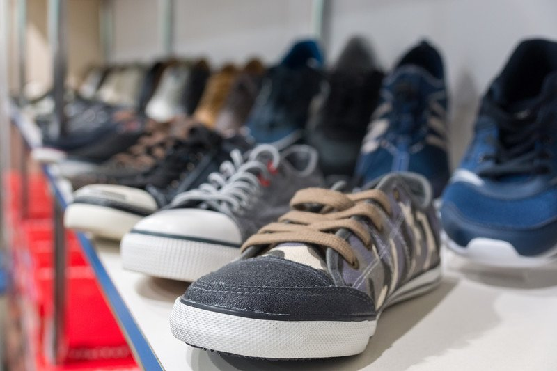 This picture shows two rows of sneakers in various styles and colors on a shelf in what appears to be a shoe shop, representing the best sneakers affiliate programs.