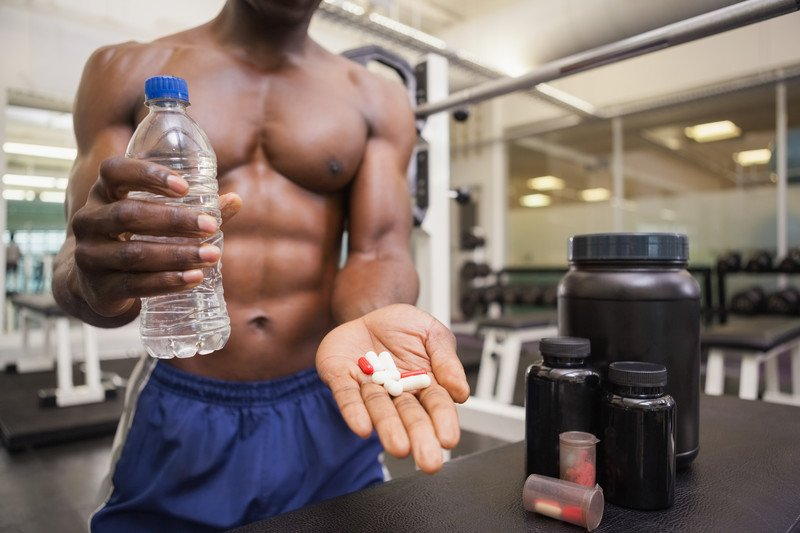 This photo shows a shirtless man in blue shorts inside a gym, holding a bottle of water in one hand and a handful of pills in the other, representing the best sport supplements affiliate programs.