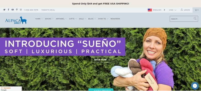 This screenshot of the home page for Alpaca Direct shows a smiling woman in a tan knitted beanie hat, standing near a tall green hedge with her arms full of Sueno skeins of yarn in a variety of colors, and in front of that is a purple text bar that introduces the 'Sueno' type of yarn.