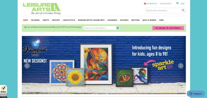 This screenshot of the home page for Leisure Arts shows a photo of a brick wall painted royal blue and a sidewalk, with some intricate diamond art pieces leaning against the wall and some text advertising new diamond art designs.