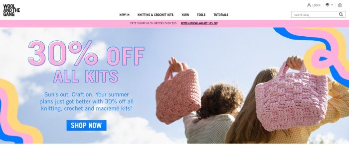 This screenshot of the home page for Wool and the Gang shows a blue sky and the backs of two women who are holding knitted bags as they walk away from the camera, along with some squiggled graphics in yellow, pink, and royal blue and a 30% off advertisement for kits in pink and blue lettering.