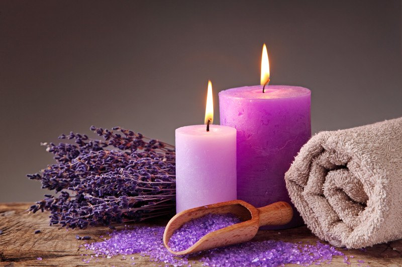 This photo shows two purple candles, a rolled up beige colored towel, a scoop of light purple bath salts and a bouquet of dried lavender on a table together.