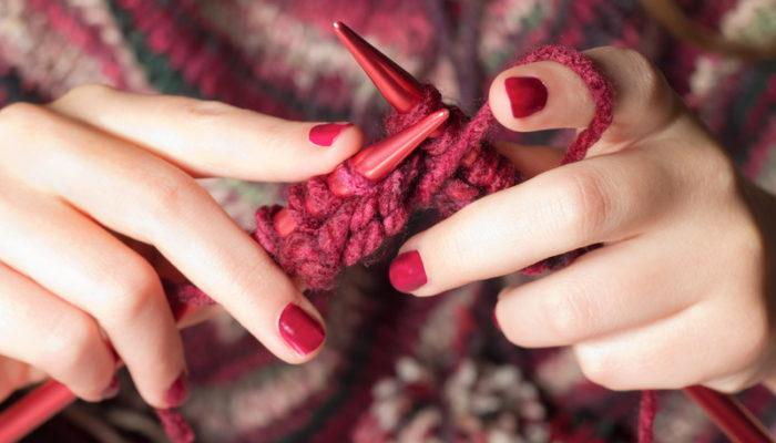 This photo shows a woman's hands with red painted fingernails, holding red knitting needles and knitting something in a red, brown, and white variegated yarn, representing the best knitting affiliate programs.