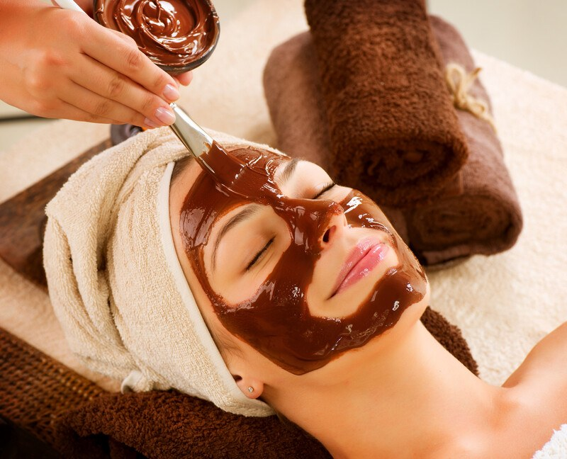 A woman with a towel over her head reclines with her eyes closed while someone paints a chocolate mask onto her face, representing the best skin care affiliate programs.