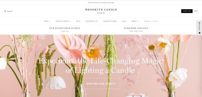 "This screenshot of the home page for Brooklyn Candle Studio shows a pink background with pink and white flowers behind white lettering that reads ""Experience the life-changing magic of lighting a candle."""