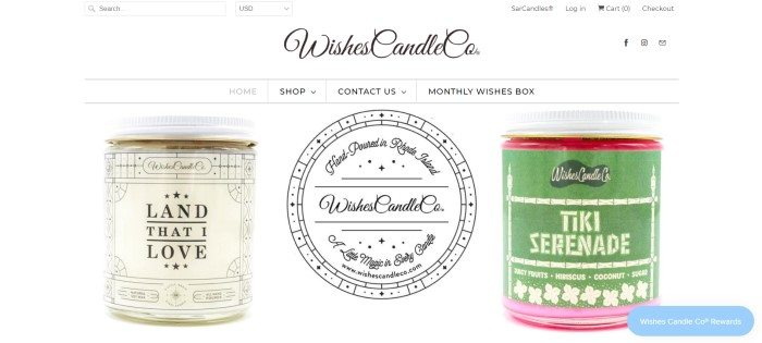This screenshot of the home page for Wishes Candle Co. shows a cream-colored candle jar on the left and a green-colored candle jar on the right on a white background, with the company logo between them.
