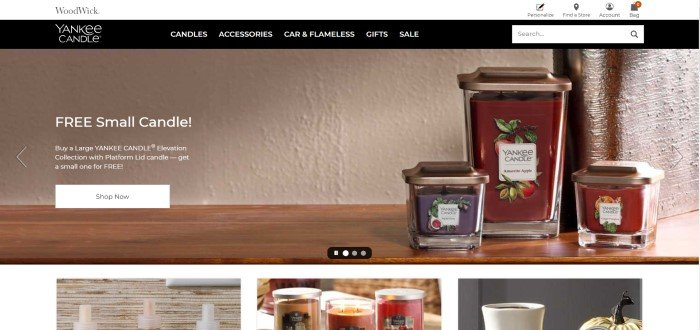 This screenshot of the home page for Yankee Candle shows three red-colored candles in jars sitting on a shelf.