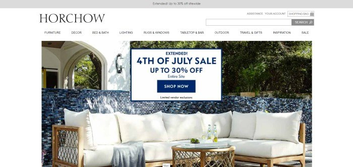 This screenshot of the home page for Horchow shows a white sectional outdoor sofa in front of a blue tiled wall and a white arched doorway, with a fourth-of-July advertisement laid over the top of the picture.