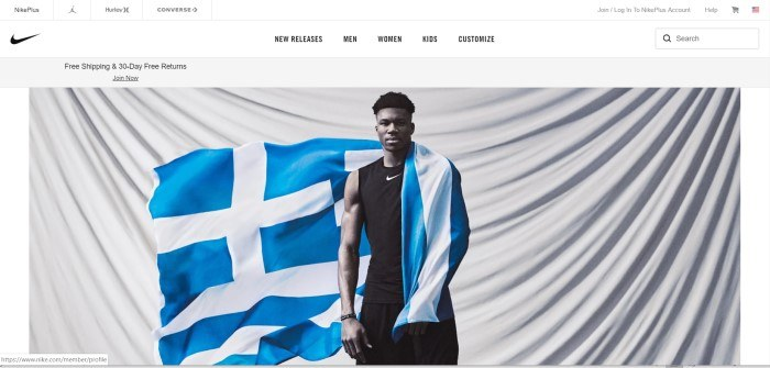 This screenshot of the homepage for Nike shows a young man wearing black Nike clothing with a blue and white flag draped around one shoulder and stretched behind him, standing in front of a large white cloth that's draped so the folds fall in a large u-shaped curve.