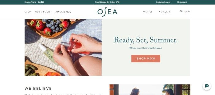 This screenshot of the homepage for OSEA has a white background, with a beige insert on the right side that includes some summer-geared text and a shopping link and a photo on the left side showing a woman's hands as she holds an OSEA product on a picnic blanket that also contains another OSEA product, a wooden tray of vegies, and a wooden tray of strawberries and blueberries.