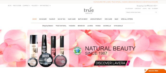 This screenshot of the home page for True Natural includes a white background almost filled with pink flower petals, along with photos of products made by the brand Lavera and an invitation in black lettering to discover the Lavera line.