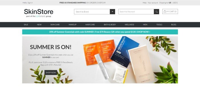 This screenshot of the home page for SkinStore has a white background, a black navigation bar, and an advertisement for a summer sale along with some skin care products in a silver tube, a blue box, an ivory box, and an orange foil packet with sprigs of plants against a gray background.