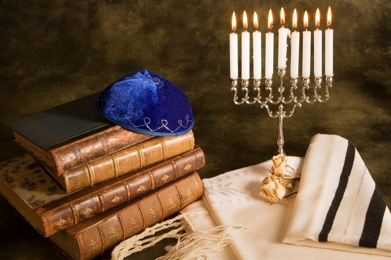 This photo has a blue yarmulka on top of a stack of four brown books, near a lit Menorah on a white cloth, representing the best Hebrew affiliate programs.