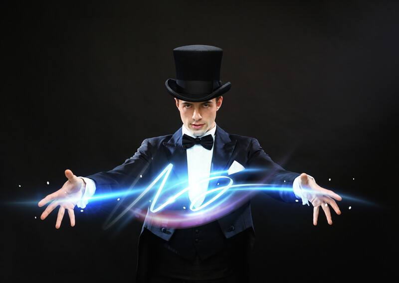 This photo shows a magician in a black suit, white shirt, black bow tie and black top hat, stretching out his arms while blue and purple lights extend from one hand to the other, representing the best magic affiliate programs.