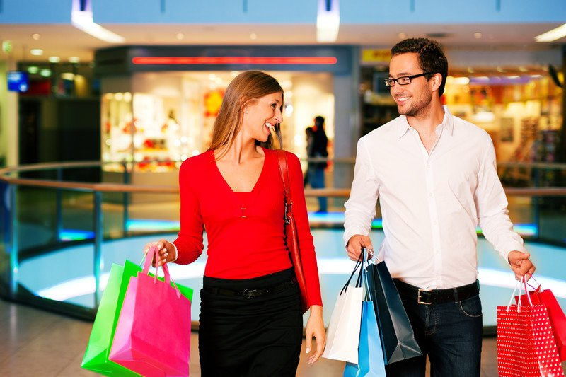 In this photo, a woman in a red shirt and a man in a white shirt walk through a shopping center together, holding brightly colored shopping bags and smiling at each other, representing the best retail affiliate programs.