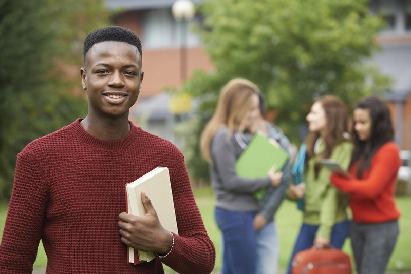 This photo shows a smiling young man in a red sweater, holding a book, while behind him three girls talk together in front of what appears to be a school building, representing the best school affiliate programs.