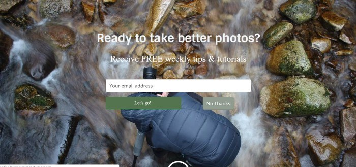 This screenshot of the home page for Digital Photography School includes a large overhead-shot photograph of a person in a black hooded jacket with a nice camera taking a picture of a rocky stream bed, along with white text reading 'Ready to take better photos?' and an opt-in bar.