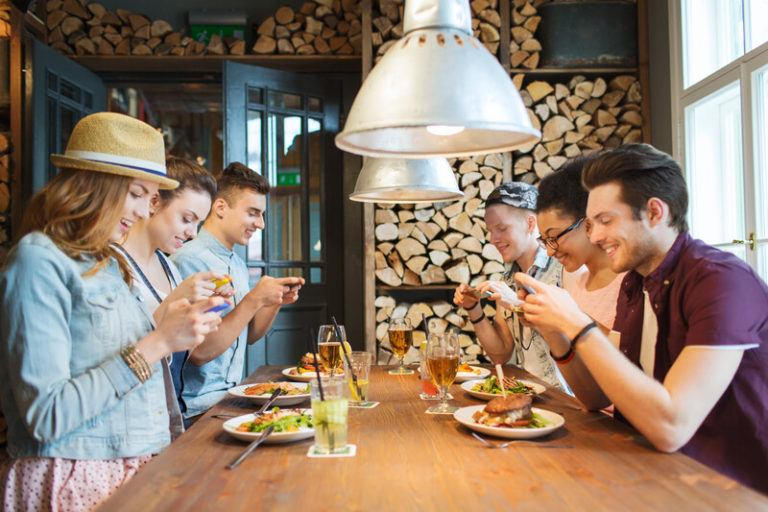 food bloggers instagramming their food at a restaurant