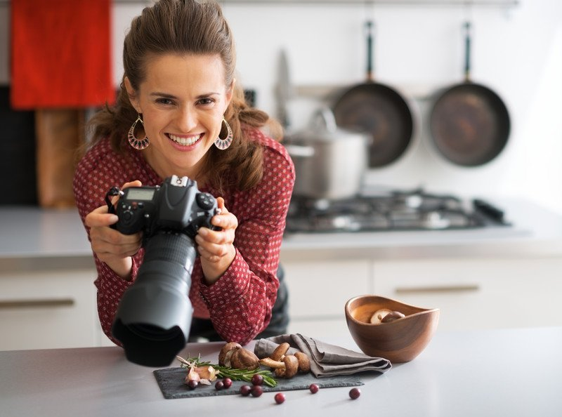 young woman with professional camera and large lens in the kitchen photographing food on the counter