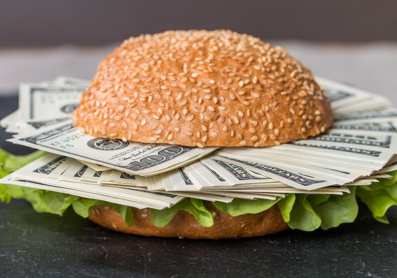 hamburger bun with lettuce and hundred dollar bills instead of meat