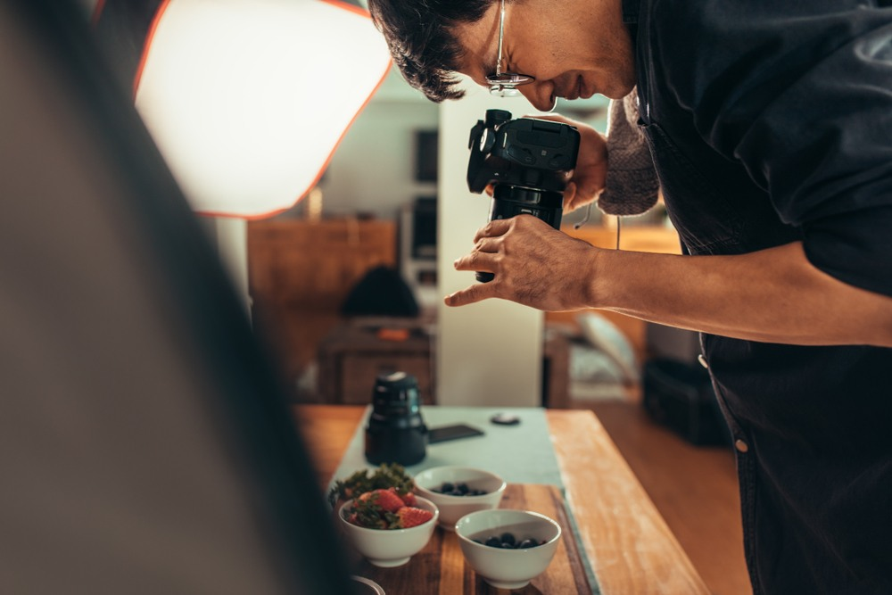 man with DSLR camera photographic dishes for his food blog