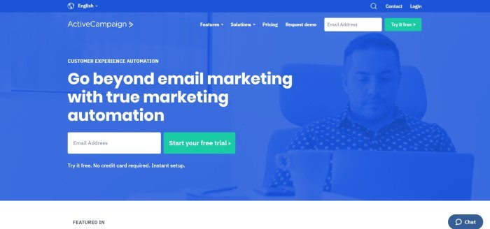 This screenshot of the home page for Active Campaign shows a dark filtered photo in royal blue of a man working at a laptop near a coffee mug, and white text that reads 'Go beyond email marketing with true marketing automation.'