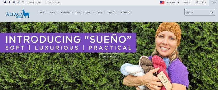 This screenshot of the home page of Alpaca Direct shows a woman in a tan beanie standing near a green hedge with her arms full of various colors of Sueno alpaca yarn.