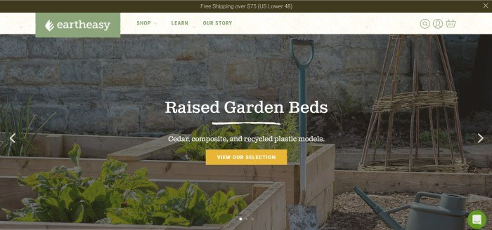 This screenshot of the home page for Earth Easy shows a row of raised garden beds in front of a stone wall, along with an advertisement in white lettering for raised garden beds.