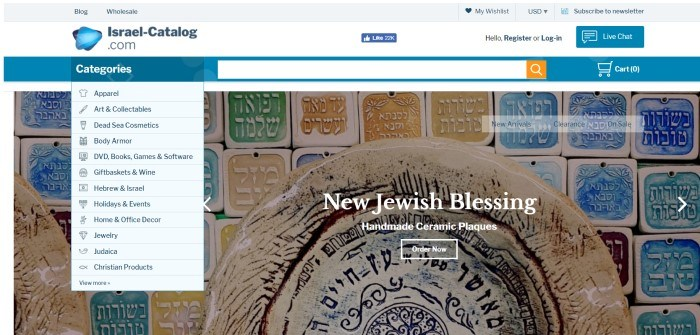 This screenshot of the home page for Israel catalog has a white background, blue header, and white drop-down text boxes with black lettering displaying the categories of goods sold here, next to a large photo of hand-made ceramic plaques with Hebrew writing on them, painted in a variety of colors.