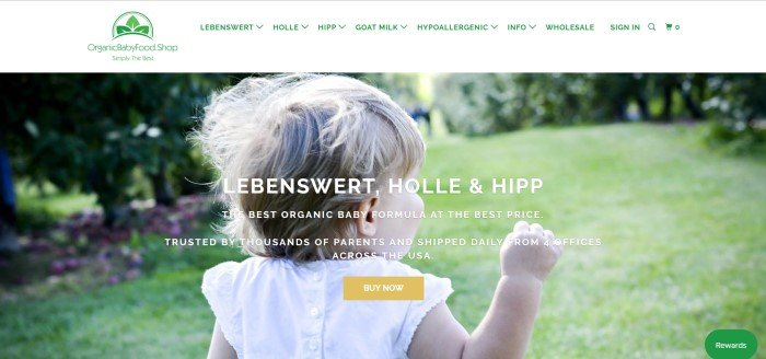 This screenshot of the home page for Organic Baby Foods includes a large photo of a blonde toddler girl in a white dress walking away from the camera across a green lawn.